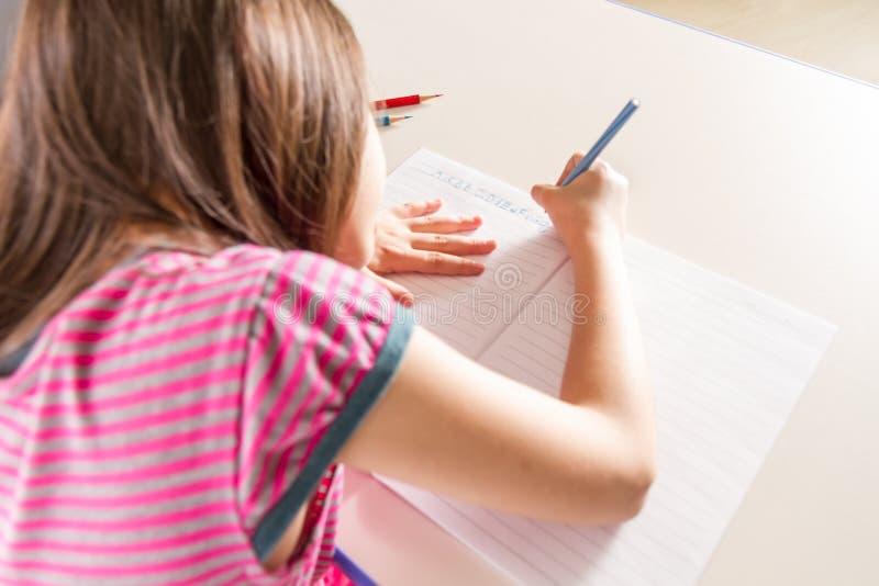 Kind die haar homwork schrijven bij een bureau met een blauw potloodkleurpotlood stock afbeelding