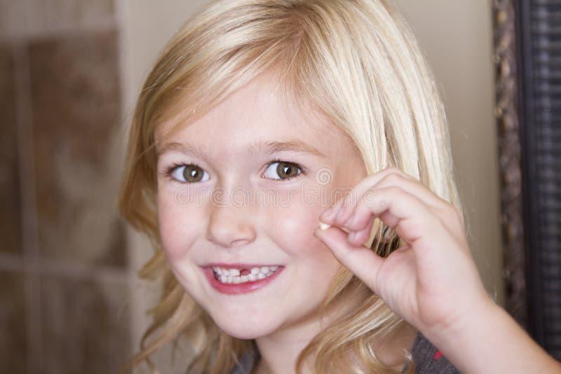 Kind die haar voortand houden stock afbeelding