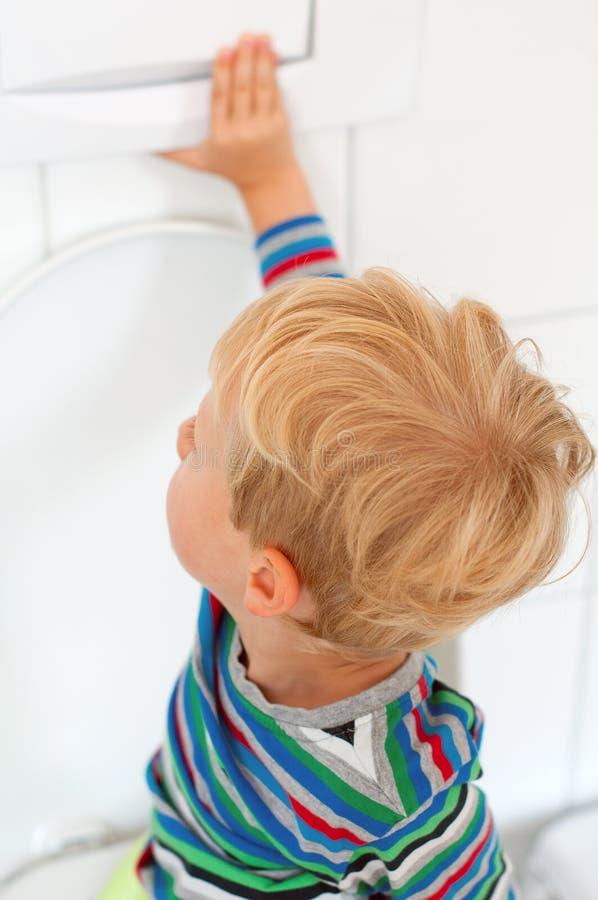 Kind die het toilet spoelen stock afbeelding