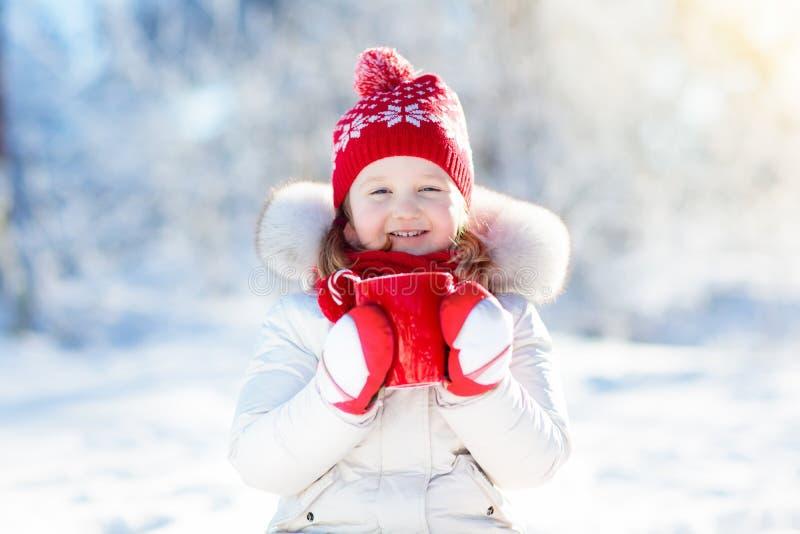 Kind die hete chocolade in de winterpark drinken Jonge geitjes in sneeuw op Chr stock foto's
