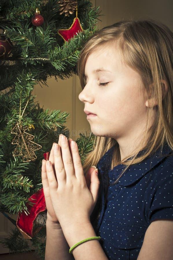 Kind die in Kerstmistijd bidden stock afbeeldingen