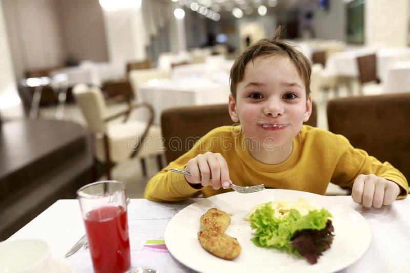 Kind die kippenkotelet eten stock foto