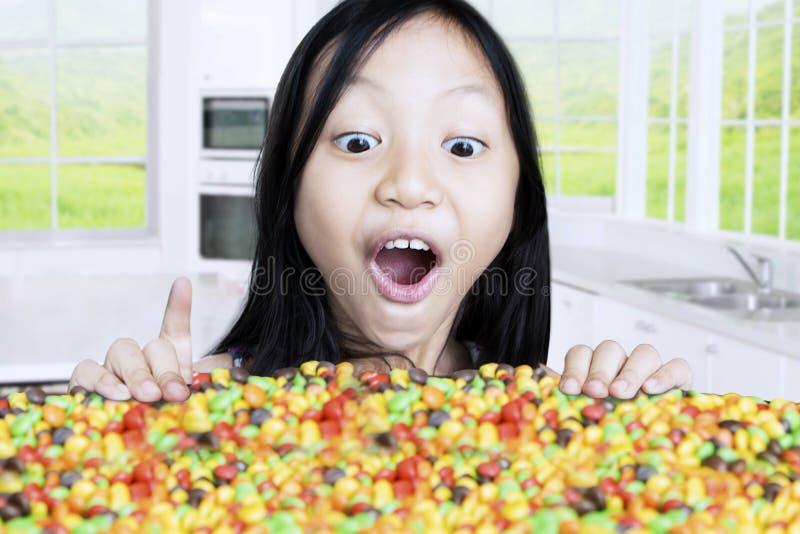 Kind die kleurrijk suikergoed in keuken bekijken stock foto's