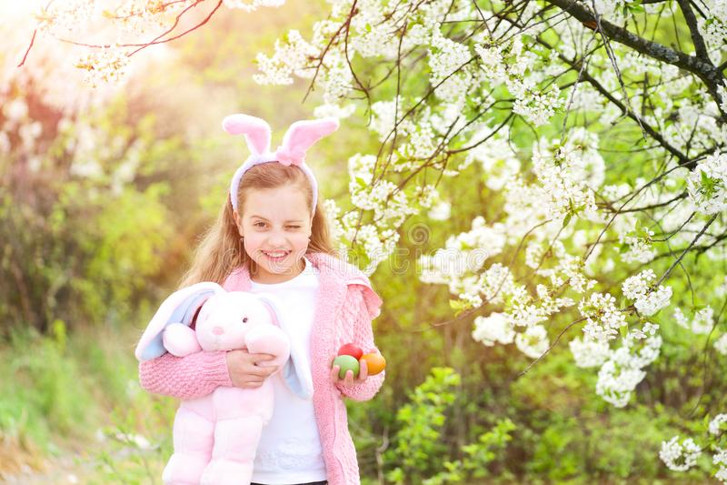 Kind die met konijntjesoren glimlachen in tuin met tot bloei komende bomen stock afbeelding