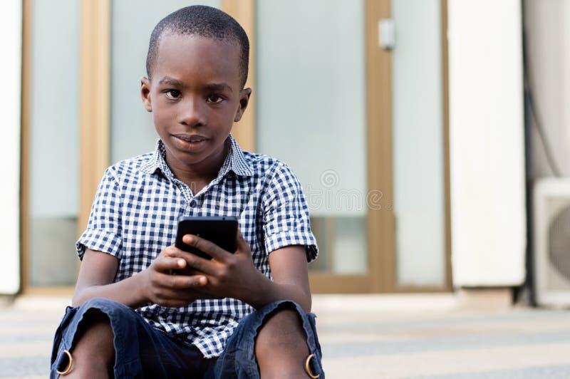 Kind die mobiele telefoon met behulp van stock foto