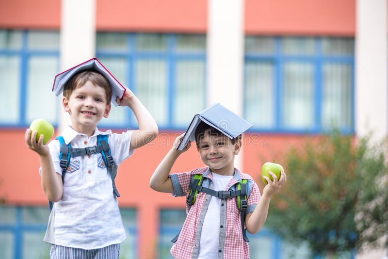 Kind die naar School gaan Jongen en zijn boeken van de vriendenholding op hoofd zoals huisdak op de eerste schooldag royalty-vrije stock afbeeldingen