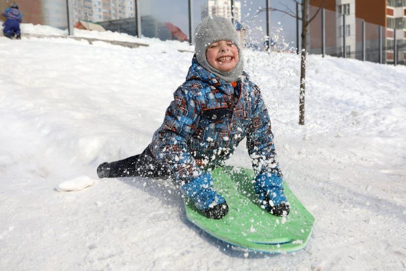 Kind die neer sledding stock afbeeldingen