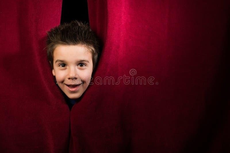 Kind die onder het gordijn verschijnen stock fotografie