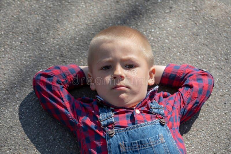 Kind die op de vloer op rug liggen, die weg lange weg kijken het nadenkende jongensportret die op gekruiste wapens liggen onderzo stock afbeeldingen