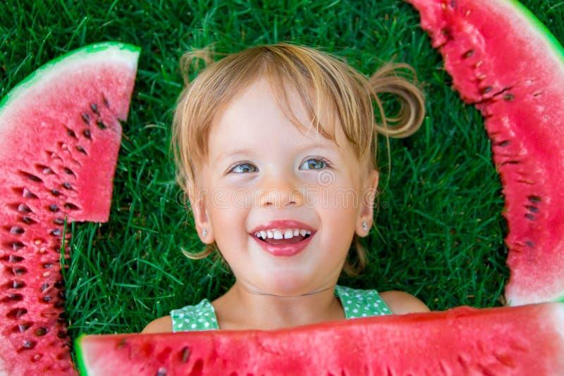 Kind die op het gras met grote plakwatermeloen in de zomertijd liggen Het glimlachen Hoogste mening royalty-vrije stock foto's