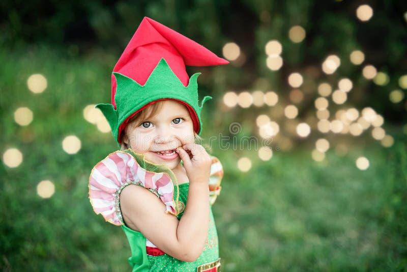 Kind die op Kerstmis in hout in juli wachten portret van kleine kinderen dichtbij Kerstmisboom Meisje dat Kerstboom verfraait stock afbeeldingen