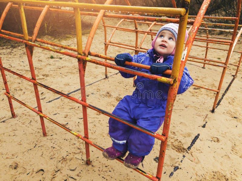 kind die op ladder bij speelplaats beklimmen stock foto