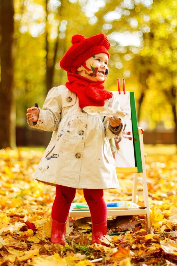 Kind die op schildersezel in Autumn Park trekken. Creatieve jonge geitjesontwikkeling stock foto