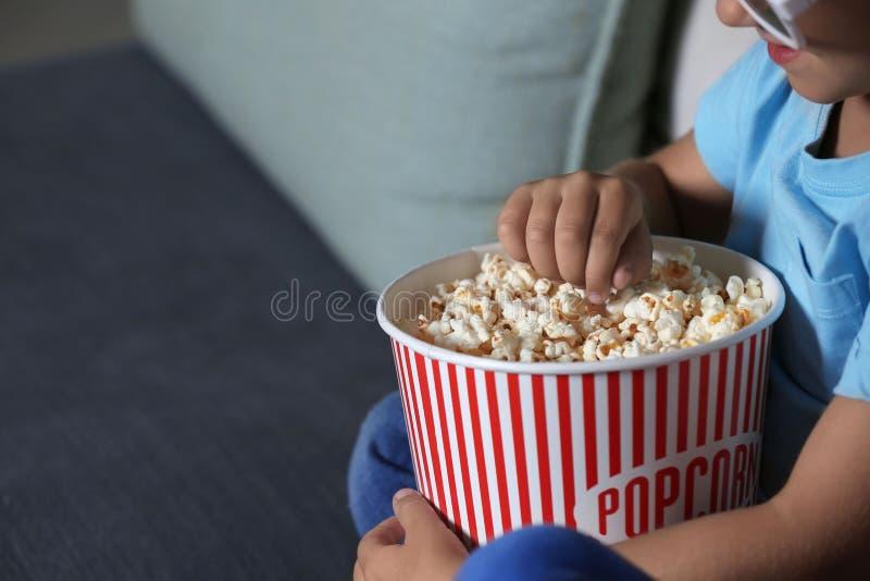 Kind die popcorn eten terwijl het letten van op TV in avond, close-up stock afbeeldingen