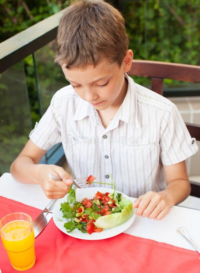 Kind die salade eten bij een koffie stock foto's