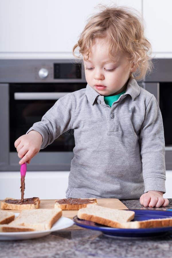 Kind die sandwich maken stock foto's