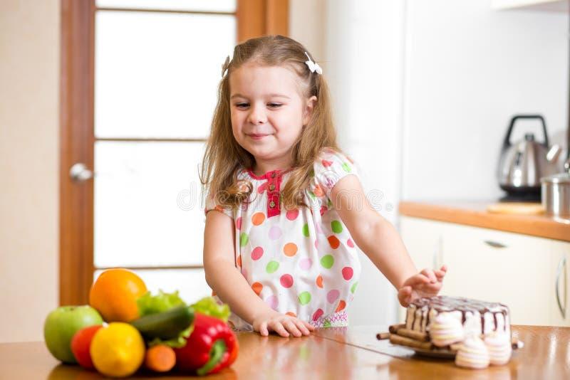 Kind die schadelijk voedsel ten gunste van groenten weigeren stock afbeeldingen