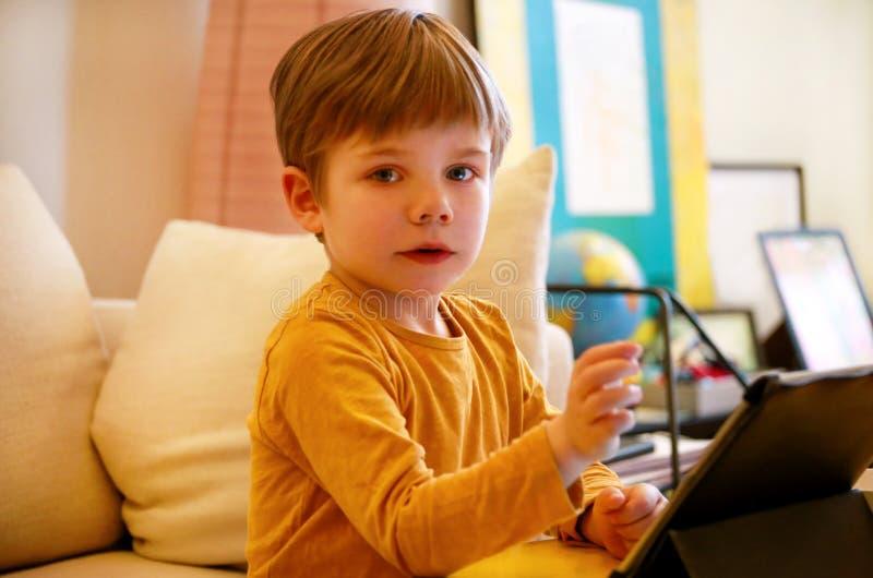 Kind die tabletpc op bed thuis met behulp van De leuke jongen op bank let op beeldverhaal, speelt spelen en leert van laptop Onde stock foto