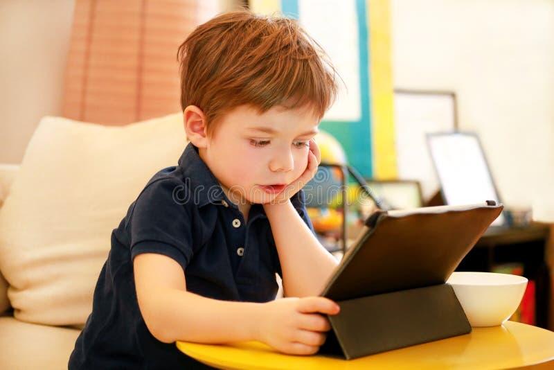 Kind die tabletpc op bed thuis met behulp van De leuke jongen op bank let op beeldverhaal, speelt spelen en leert van laptop Onde stock afbeelding
