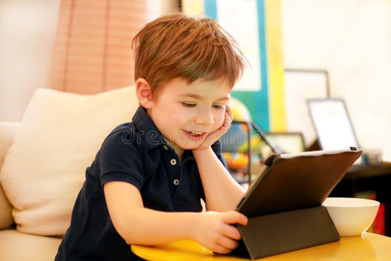 Kind die tabletpc op bed thuis met behulp van De leuke jongen op bank let op beeldverhaal, speelt spelen en leert van laptop Onde royalty-vrije stock fotografie