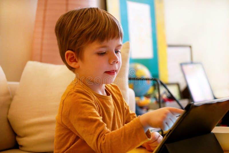 Kind die tabletpc op bed thuis met behulp van De leuke jongen op bank let op beeldverhaal, speelt spelen en leert van laptop Onde royalty-vrije stock foto's