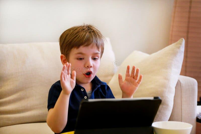 Kind die tabletpc op bed thuis met behulp van De leuke jongen op bank let op beeldverhaal, speelt spelen en leert van laptop Onde royalty-vrije stock afbeeldingen