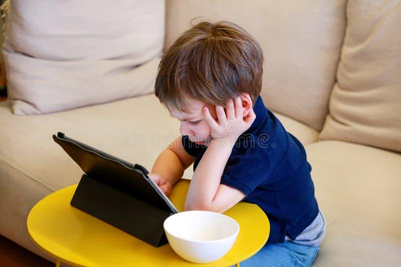 Kind die tabletpc op bed thuis met behulp van De leuke jongen op bank let op beeldverhaal, speelt spelen en leert van laptop Onde royalty-vrije stock afbeelding