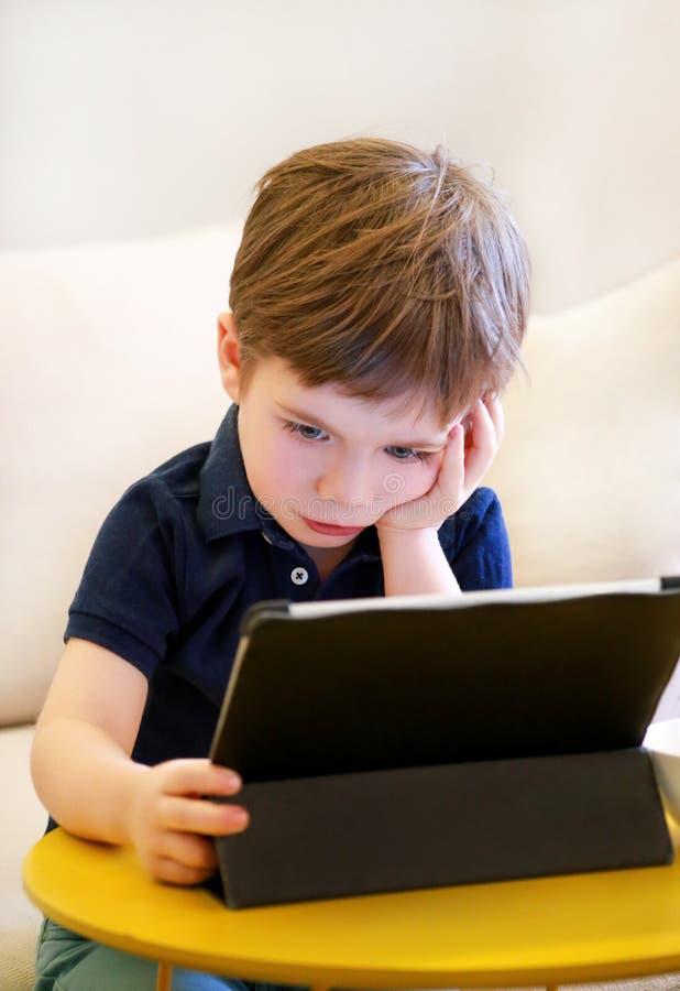 Kind die tabletpc op bed thuis met behulp van De leuke jongen op bank let op beeldverhaal, speelt spelen en leert van laptop Onde stock afbeeldingen