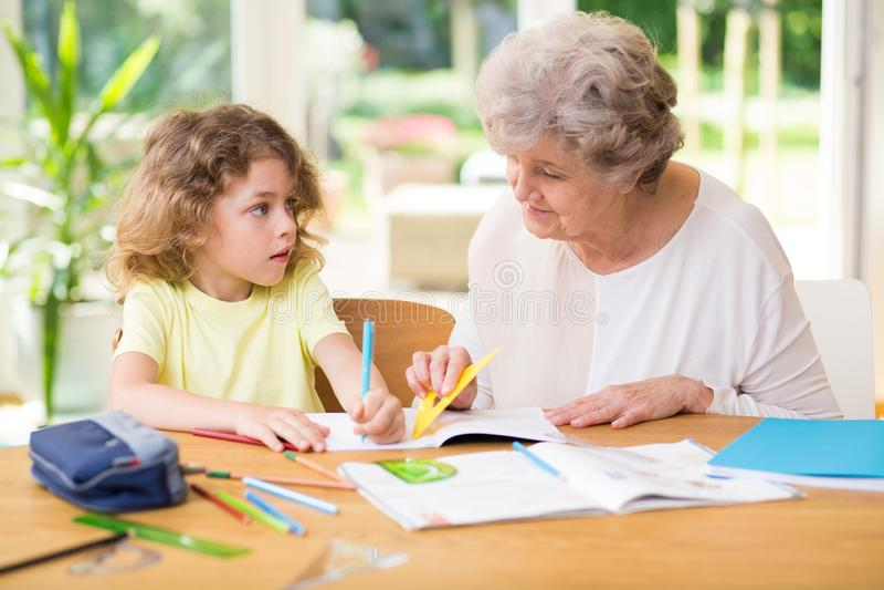 Kind die thuiswerk met zijn grootmoeder doen stock afbeelding