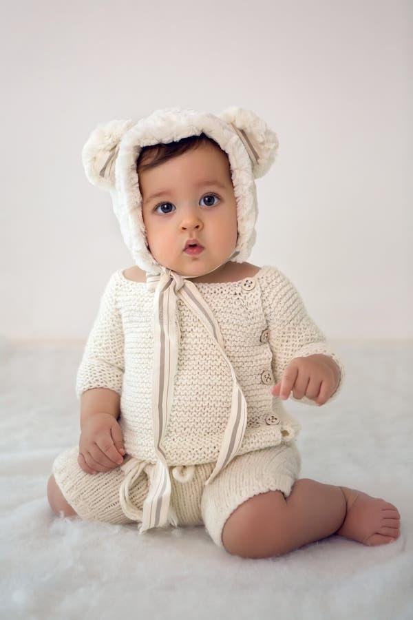 Kind die van acht maanden in de studio in een hoed zitten stock fotografie