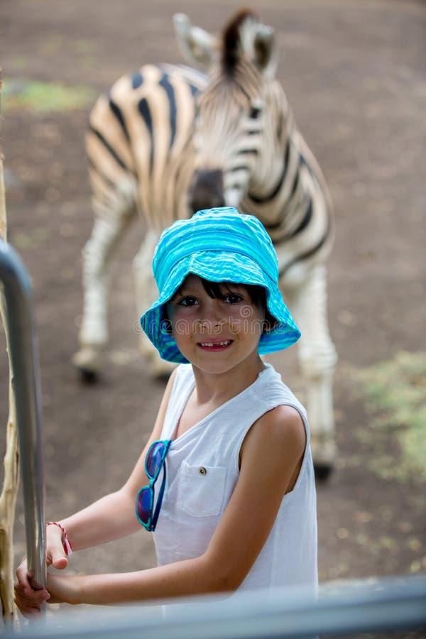 Kind die van kudde van zebras en struisvogel in de wildernis in park genieten stock afbeeldingen