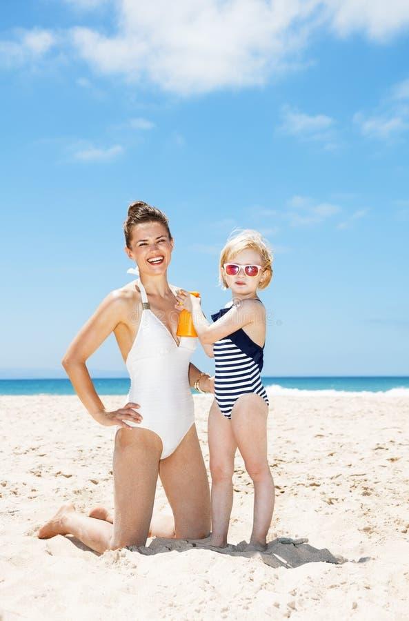 Kind die zonnescherm op glimlachende moeder in zwempak toepassen bij strand royalty-vrije stock afbeeldingen