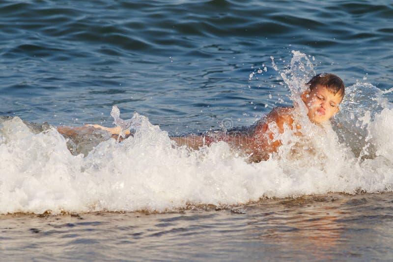 Kind door een overzeese golf wordt geraakt die stock foto's