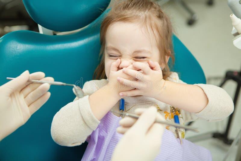 Kind door het sluitenogen en mond die van tandartseninstrumenten bang wordt gemaakt royalty-vrije stock afbeelding
