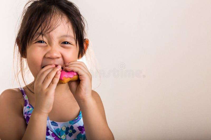 Kind Doughnut eten/Kind die Doughnutachtergrond eten stock afbeeldingen