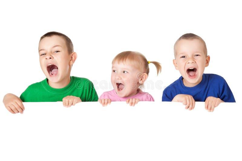 Kind drei hinter weißem Vorstand stockbilder