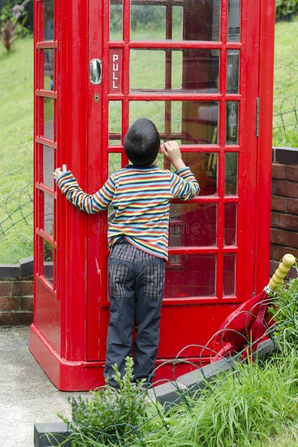 Kind durch einen Brithish-Telefonkasten lizenzfreie stockfotos