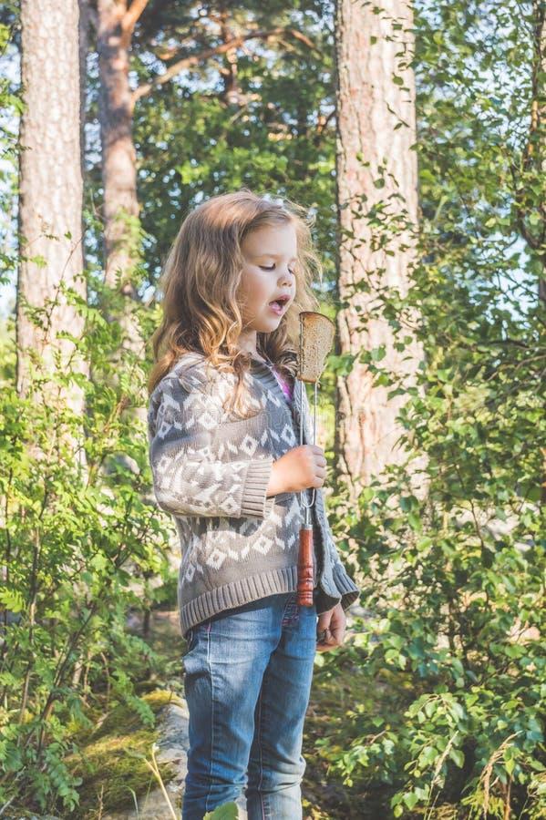 Kind in een stijging in het hout die gebraden brood op de brand eten royalty-vrije stock foto