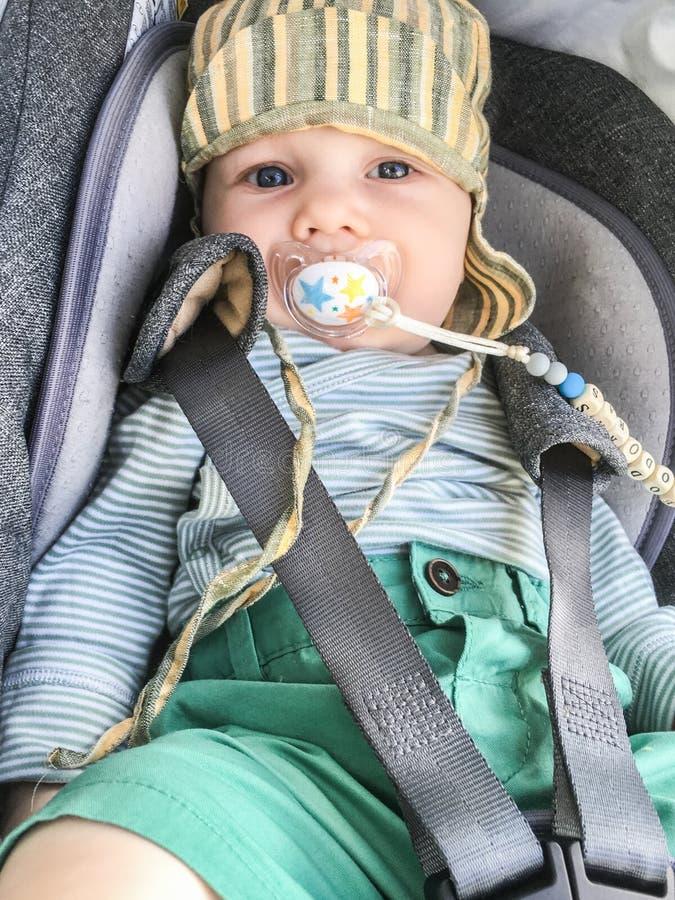 Kind in einem Autositz mit der Attrappe des Babys lizenzfreies stockfoto