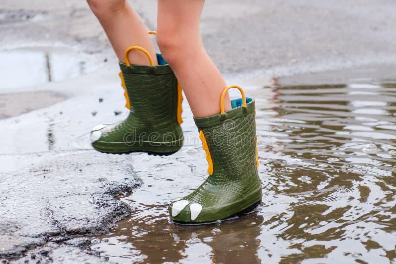Kind in einem Grün lädt das Springen in Pfützen auf Ein Junge steht im Regen, ein heller Regenmantel Spaß im Freien durch irgende lizenzfreie stockfotos