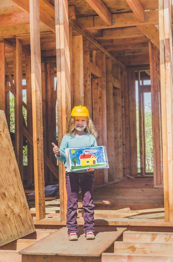 Kind in einem Sturzhelm auf der Baustelle eines Holzhauses lizenzfreies stockfoto