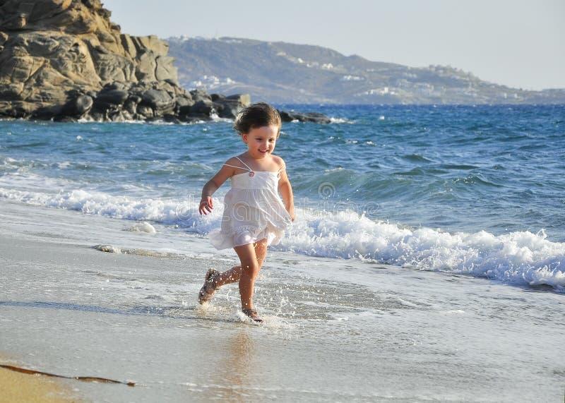 Kind in einem weißen Kleid, das durch die Wellen läuft stockfotos
