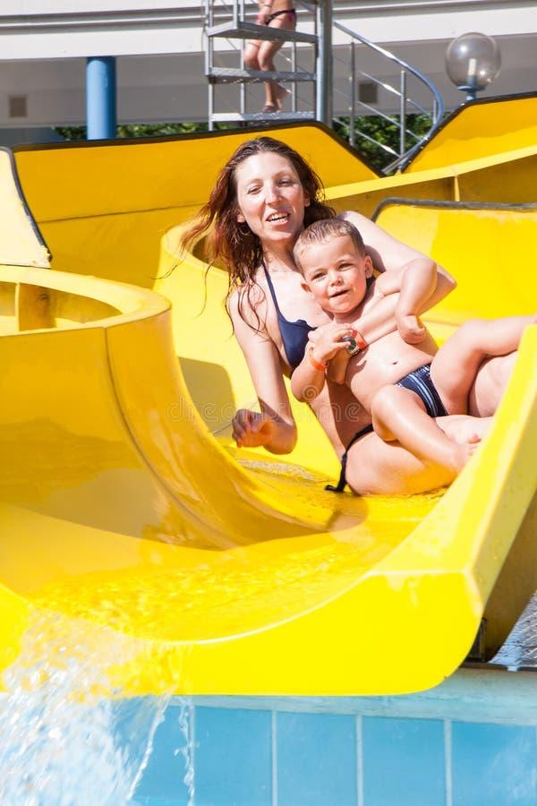 Kind en mamma het spelen met de dia in de pool royalty-vrije stock foto