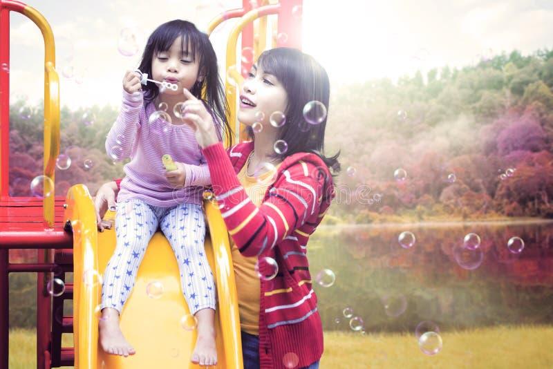 Kind en moeder het spelen zeepbel op dia stock fotografie