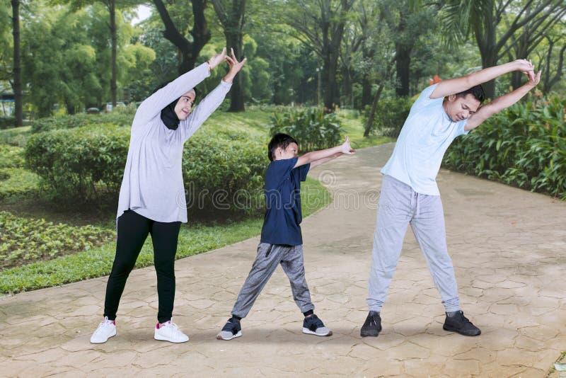 Kind en ouders die handenrek in het park doen royalty-vrije stock afbeeldingen
