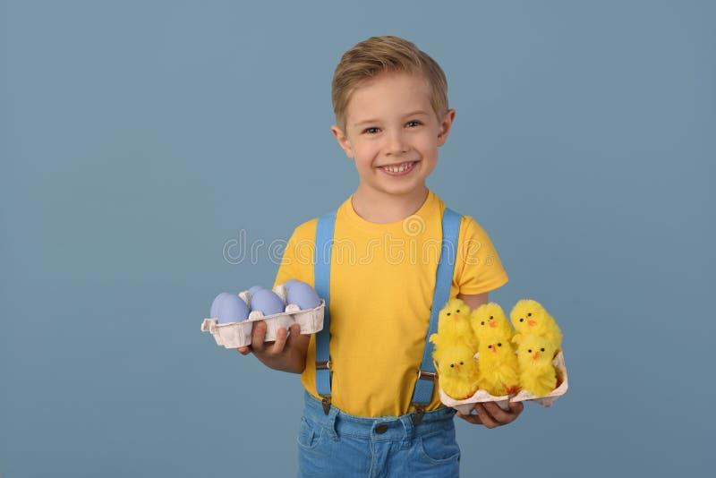 Kind en Pasen De glimlachende blonde jongen, 6 jaar oud, houdt kleureneieren stock afbeelding