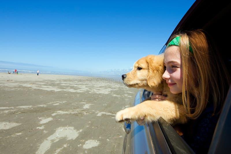 Kind en puppy bij het strand royalty-vrije stock afbeelding