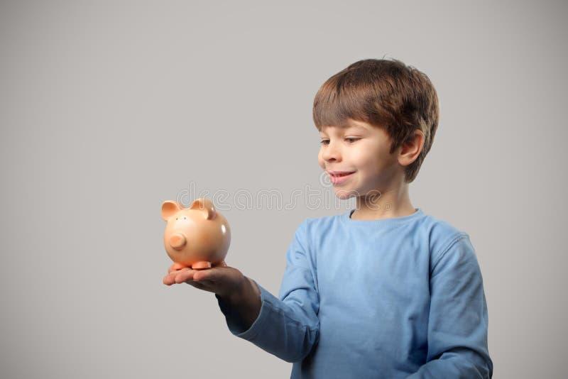 Kind en spaarvarken stock afbeeldingen