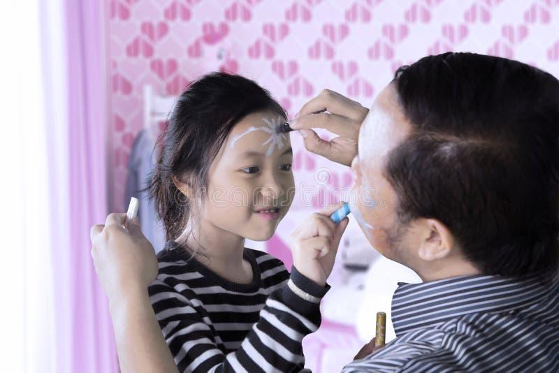 Kind en vader die gezicht het schilderen doen stock foto's
