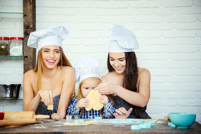 Kind en vrouwen die vorm voor koekje in deeg snijden stock afbeelding